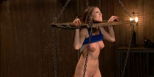 Brunette With Locked Limbs In Stocks